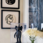 Kaws' <i>Companion Black Colorway Figurine</i> Stands Among Two Framed Ceramic Plates By Picasso And Chuck Close's <i>Self Portrait</i> In Shades Of Gray.""